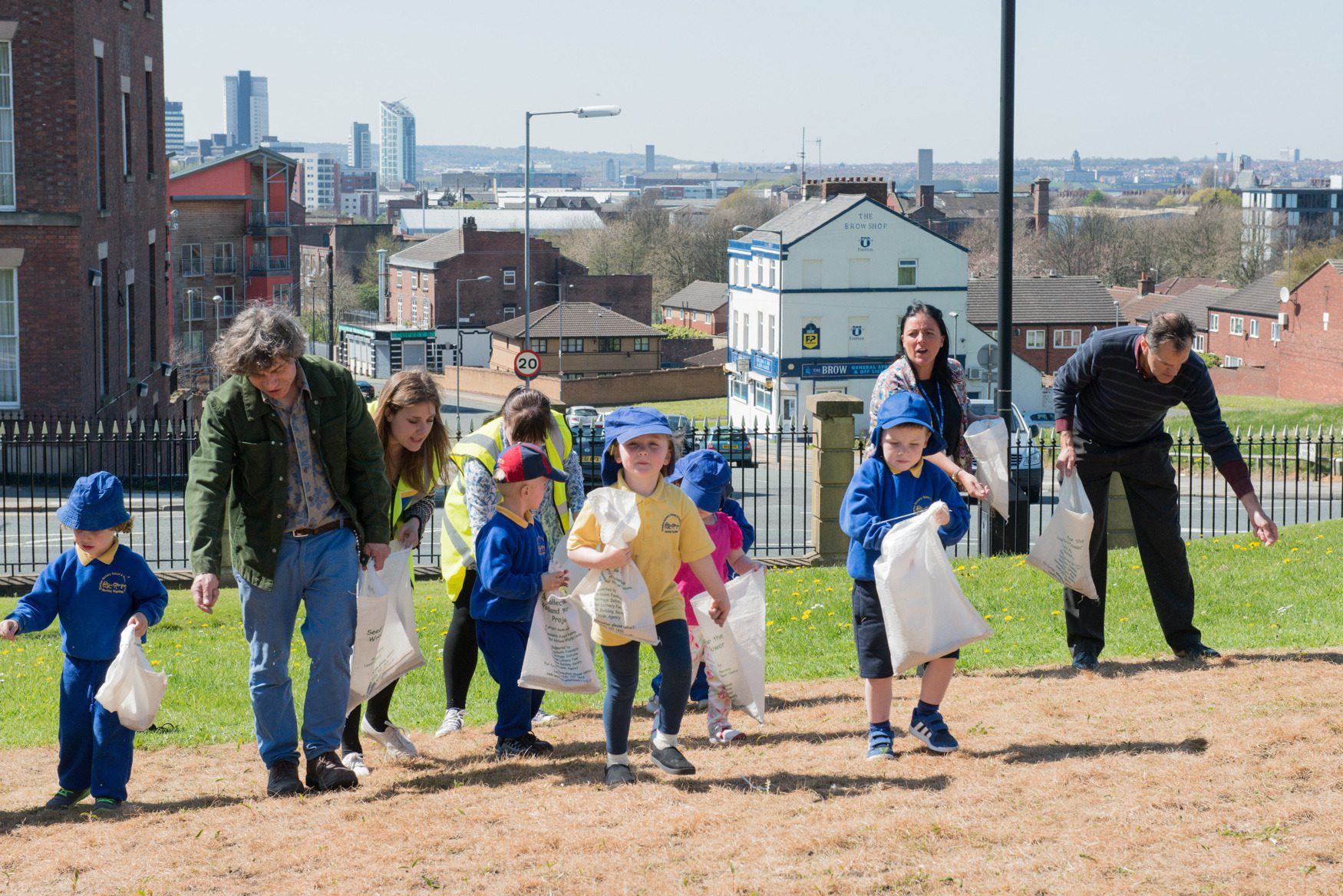 Children and local community members volunteering at The Land Trust's Liverpool site, Everton Park. Sowing seed for a wildflower meadow to improve their local green space.